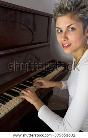 Blond short hair woman woman with white Tshirt playing piano - stock photo