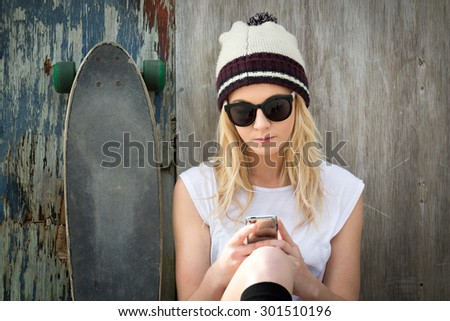 Blond skater girl text messaging listening to music - stock photo