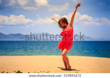 blond slim girl in short red frock dances barefoot on sand beach hands above against azure sea wind shakes long hair - stock photo