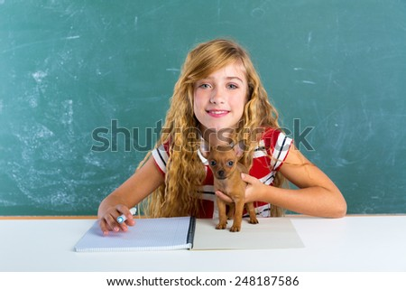 Blond student girl with puppy dog at class green chalk board sitting in desk - stock photo