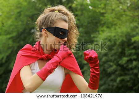 Blond super hero with red cape and red gloves is ready to fight