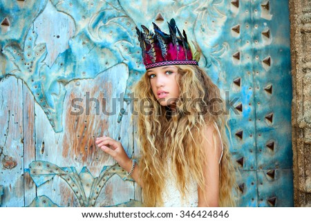 Blond teen girl tourist in Mediterranean old town door with colorful feathers on hair - stock photo