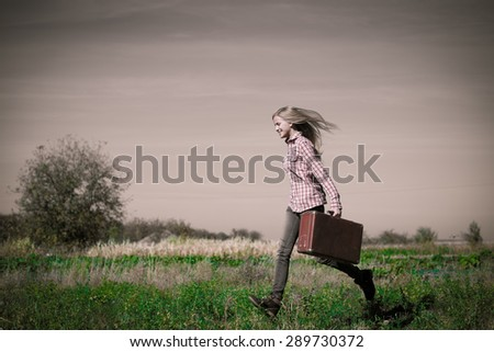 Blond teenage girl walking fast carring retro suitcase over rural background copyspace on summer cloudy day - stock photo