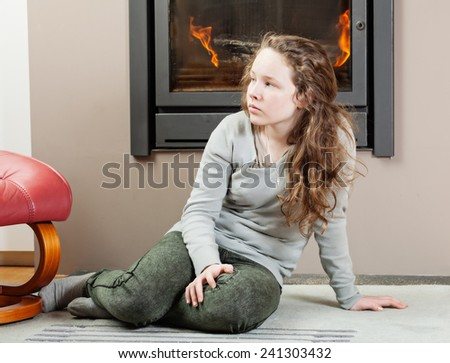Blond thoughtful teenager girl sitting on carpet near fireplace