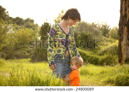 blond toddler son hug his mother in green outdoor