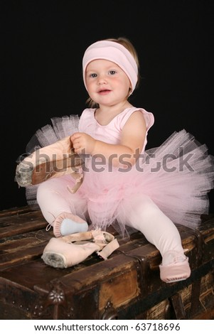 Blond toddler wearing a tutu holding pointe shoes - stock photo