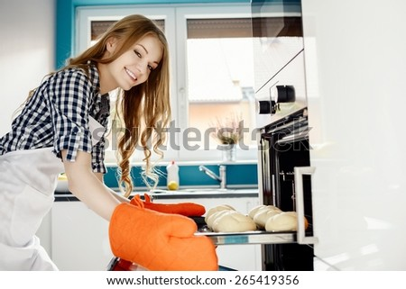 Blond woman baking a bread rolls in kitchen oven. She pulls rolls from the oven. Hands protected by orange kitchen gloves.  - stock photo