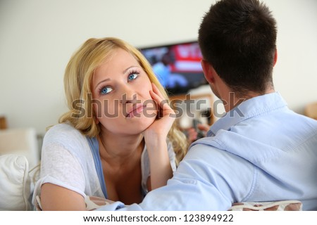 Blond woman being bored watching tv ith boyfriend - stock photo