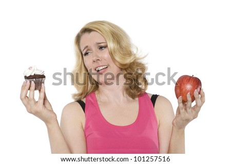 Blond woman decides between a cupcake and an apple