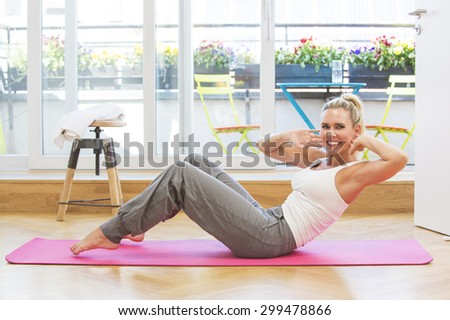 blond woman doing yoga in her living room - stock photo