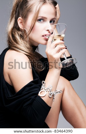 blond woman drinking martini, studio shot