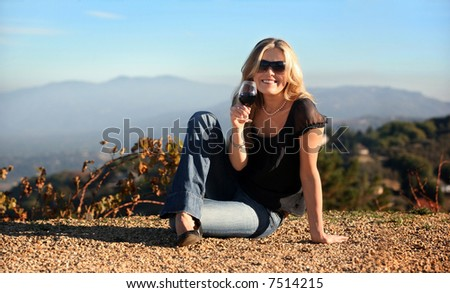 Blond woman enjoying wine at the winery - stock photo
