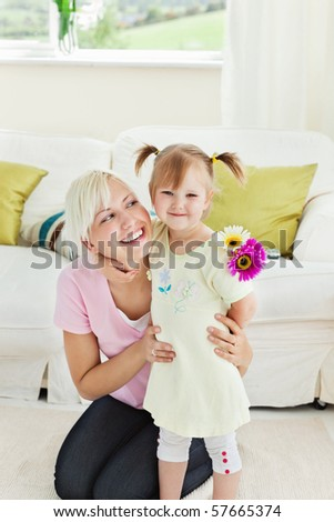 Blond woman get surprise by her daughter in living room - stock photo