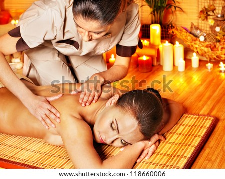 Blond woman getting by candlelight massage in spa. - stock photo