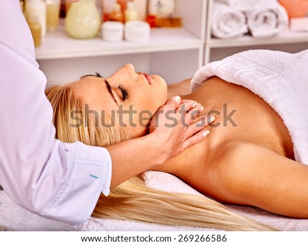 Blond woman getting head massage at spa. - stock photo