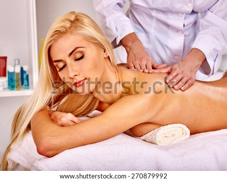 Blond woman getting massage in health resort. Girl lying on her stomach. - stock photo