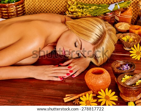 Blond woman getting massage in tropical spa on wooden board.