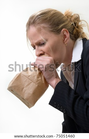 Blond woman holding a brown paper bag over mouth with a distraught expression as if having a panic attack or being nauseated