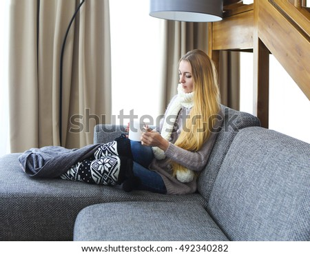 Blond woman holding a cup of warm tea while relaxing on the sofa