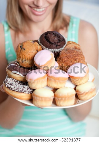 Blond woman holding a plate of cakes at home - stock photo