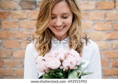 Blond woman holding flowers outdoors