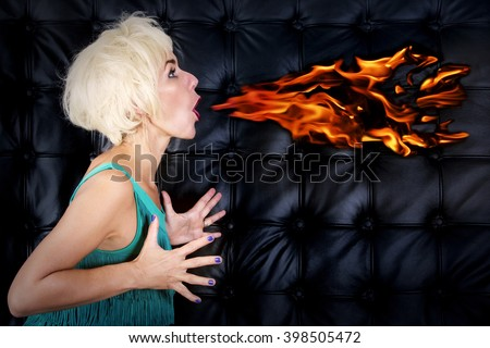 blond woman in green dress spitting fire out of her mouth in front of black leather background - stock photo