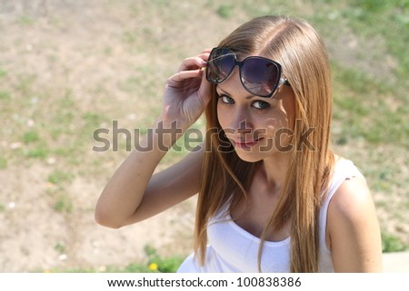 Blond woman in jeans and dark glasses standing on an outdoor summer patio - stock photo
