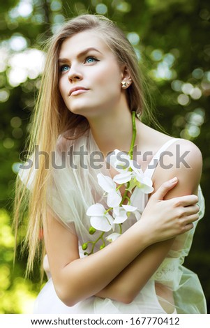 blond woman in white among trees
