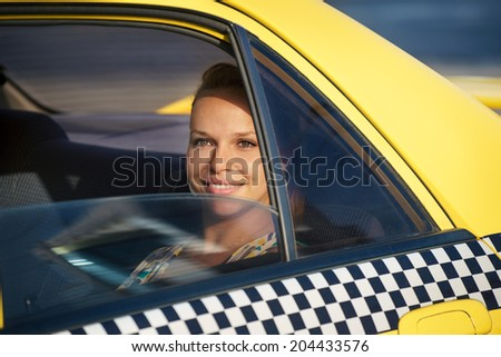 blond woman in yellow taxi looking out of car window and smiling. Tourism and business travel  - stock photo