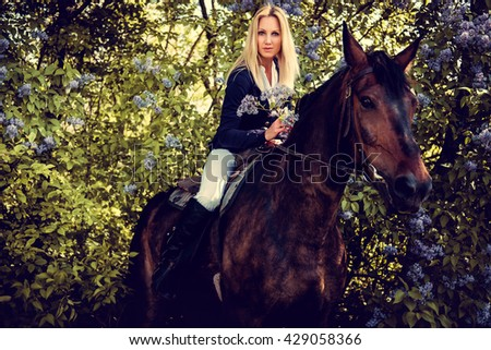 Blond woman jockey sitting on horse back.