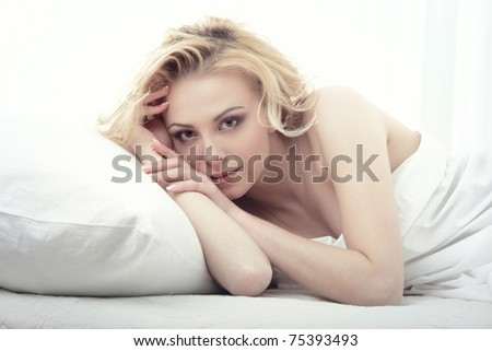Blond woman laying on the bed on a white background