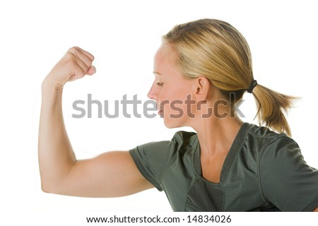 Blond woman looking at her arm muscles. Portion of photographers commission of this image will be donated to Autism Ontario.