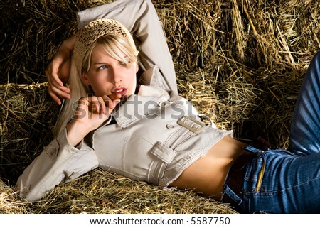 blond woman lying down on haystack - stock photo