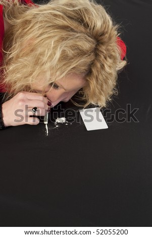 Blond woman on a tableau of cocaine - stock photo