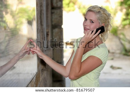 Blond woman outside restaurant using mobile telephone - stock photo