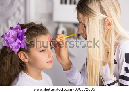 Blond woman paints the face of a girl - stock photo