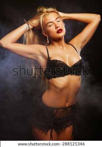 blond woman posing in lingerie over dark background - stock photo