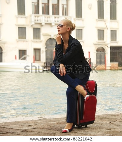 Blond woman sitting on a suitcase - stock photo