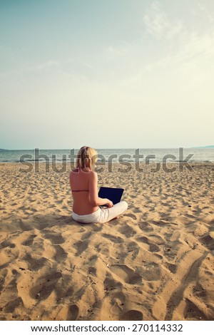 blond woman sitting on sunny beach with laptop - stock photo