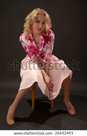 Blond woman sitting on wooden stool