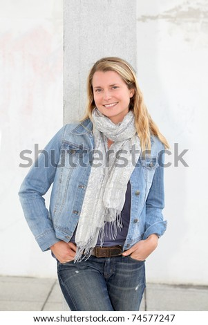 Blond woman standing on concrete wall - stock photo