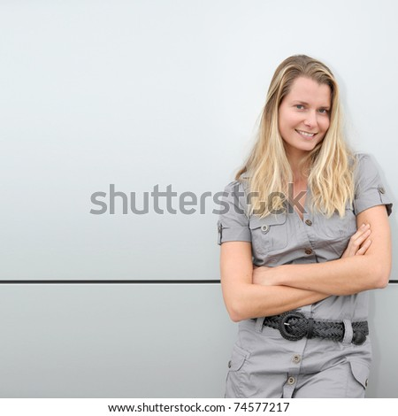 Blond woman standing on grey background - stock photo