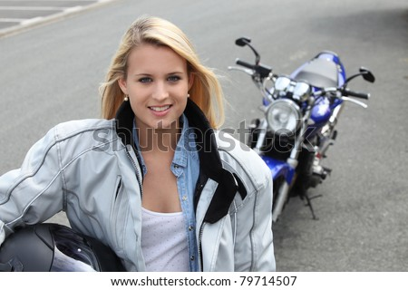 Blond woman stood by motorbike - stock photo