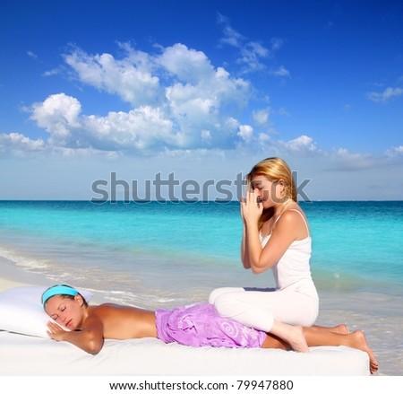 blond woman therapist in Caribbean beach doing meditation shiatsu massage in paradise - stock photo