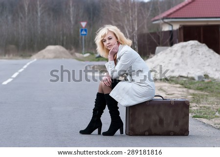 blond woman waits sitting on a suitcase