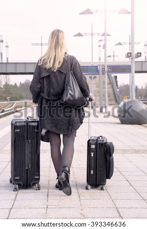 blond woman walking at train station with her suitcases - stock photo