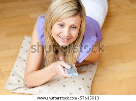blond woman watching TV holding a remot lying on the floor