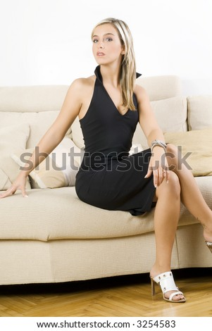 blond woman wearing a black dress and sitting on the sofa in her living room