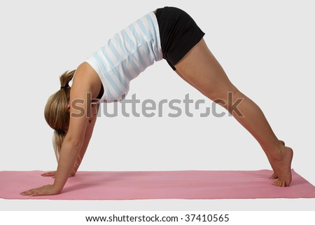 Blond woman wearing exercise attire doing yoga stretch on pink mat over white - stock photo