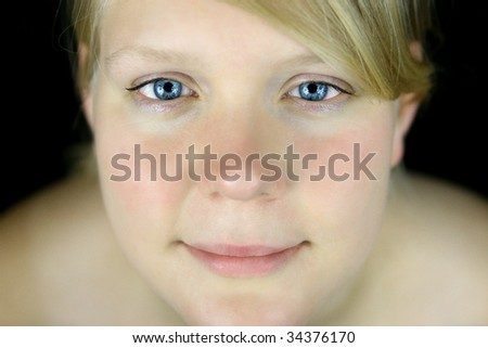blond woman with blue eyes before black background